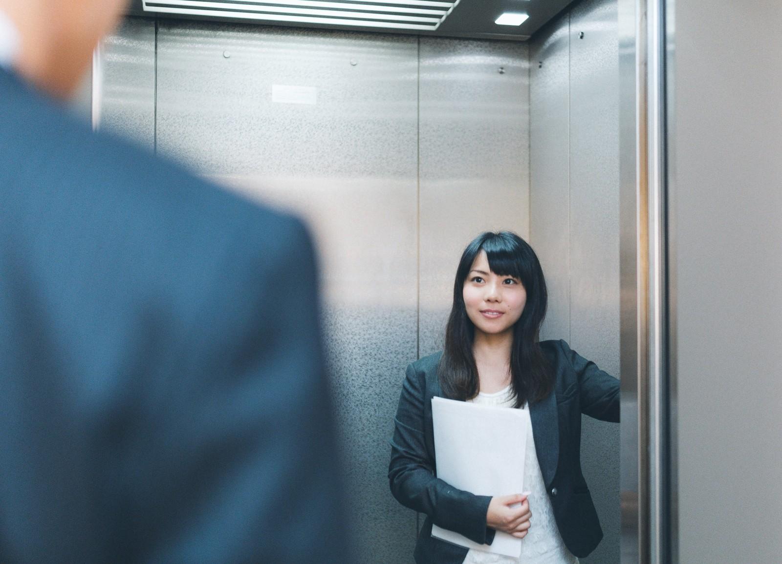 エレベーターで案内する女性